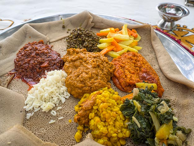 The most famous vegetarian Ethiopian cuisine, fasting Yetsom Beyaynetu platter served on a huge sheet of Injera