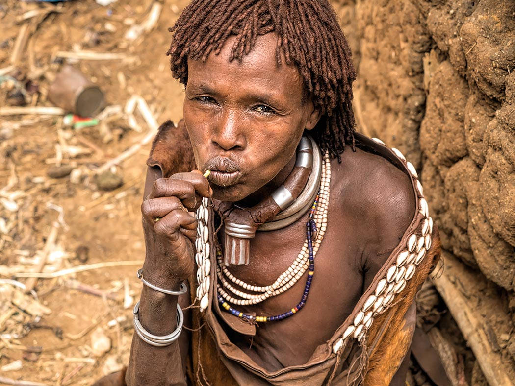 A Hamer tribe woman in southern Ethiopia picks her teeth with a twig of Neem while selling butter at the local market in Turmi