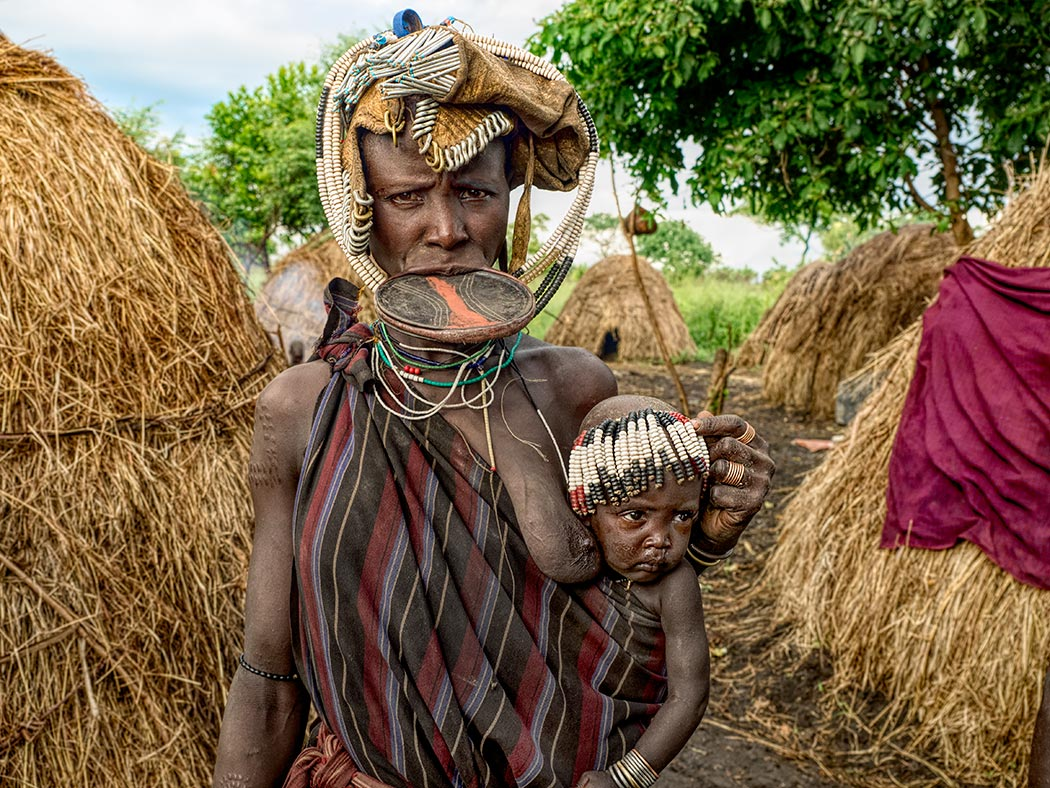 Woman and child from the Mursi tribe in southern Ethiopia. The woman is wearing a lip plate that stretches out her lower lip, making her more attractive and thus more marriageable.