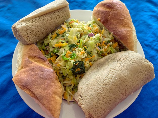 Cabbage, carrot, and spinach salad with Injera and wheat rolls