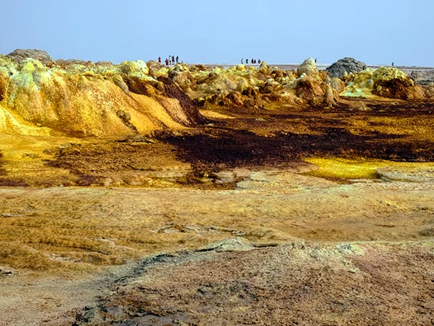 Otherworldy landscape in the Dallol hydro-geothermal sulfur fields. Note the people atop the cliff to get a feeling for the immnsity of the place.