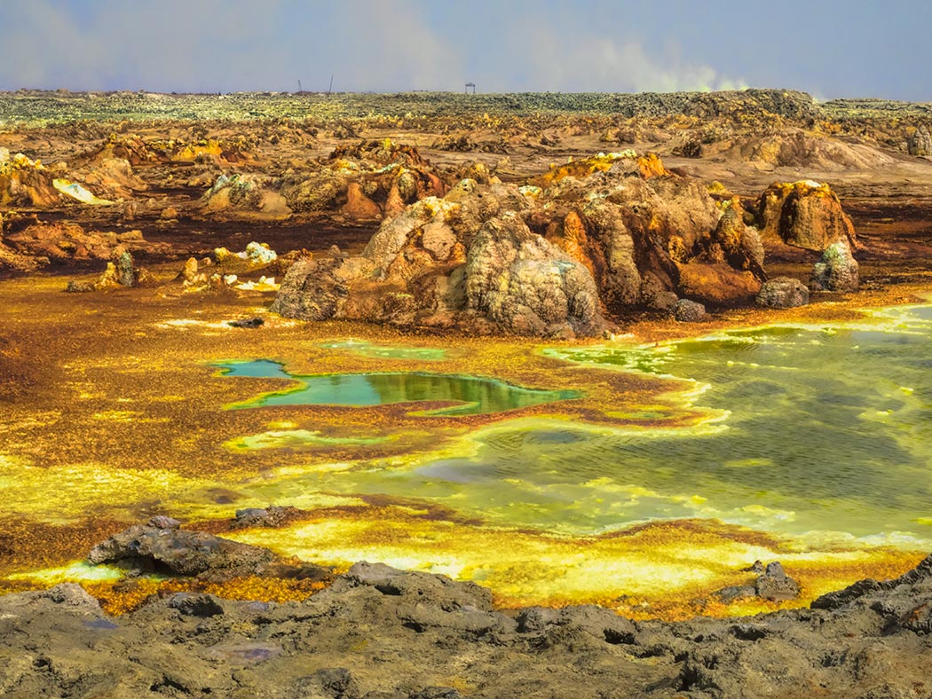 Dallol, officially one of the remotest places on earth, is located in the Danakil Depression in northeast Ethiopia. It is known for its otherworldly hydro-geothermal features that include acidic sulfur lakes, geysers, and bizarrely colored mineral deposits.