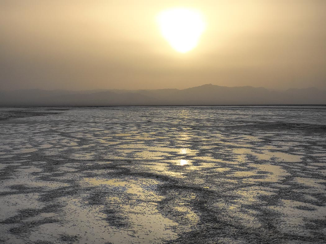 Sun sets over the salt flats in the Danakil Depression of Ethiopia, one of the lowest and hottest places on Earth