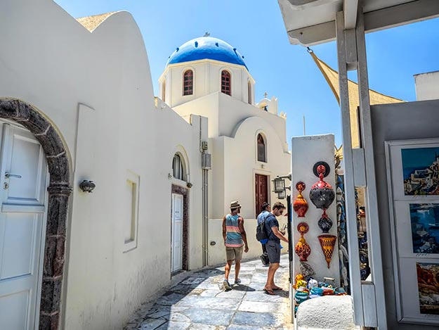Marble-paved main street of Oia, Santorini, features the village's famous whitewashed houses and blue dome