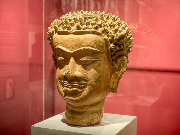 Terracotta Buddha head done in the Hariphunchai style, which featured a solemn face, long and bulging eyebrows, and a carved area above the lip that resembles a mustache. On display at the Haripunchai National Museum in Lamphun, Thailand.
