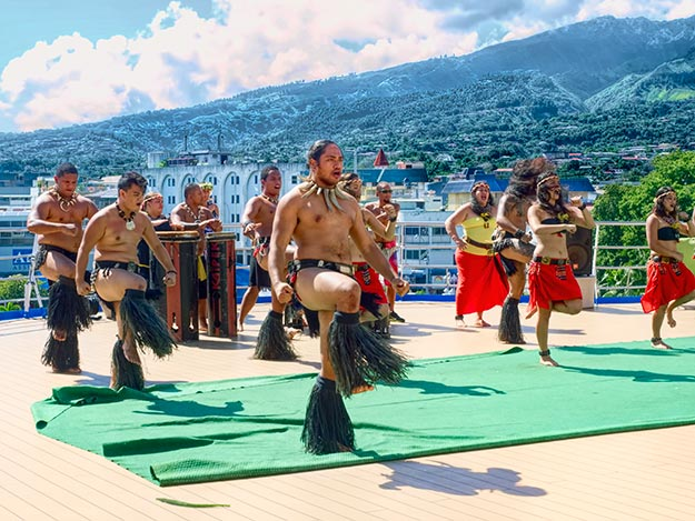 Traditional Marquesan dancers perform on the pool deck as the ship departs Tahiti