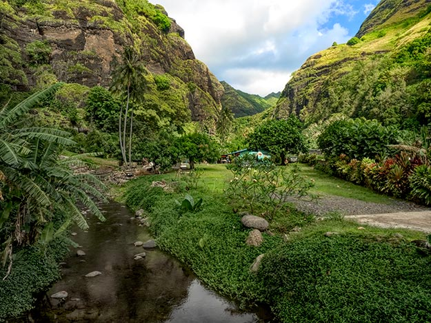 Lush valley bracketed between craggy mountains on the island of Fatu Hiva