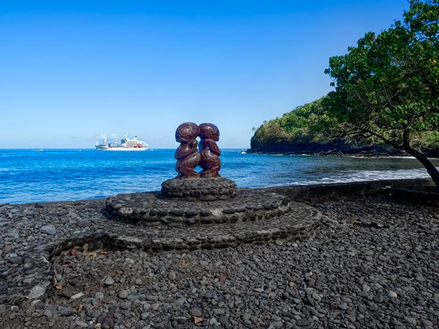 Carved wooden Tikis stand sentinel near the dock on the Marquesan island of Fatu Hiva