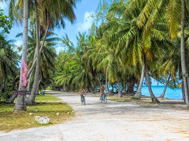 Biking along the main street in the village of Roulotte on Fakarava Island, in the Tuamoto Archipelago of French Polynesia