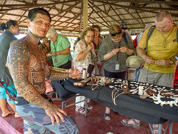 I bought a Tiki carved from cow bone from this artist, who then posed for a picture of his full-body Polynesian tattoos