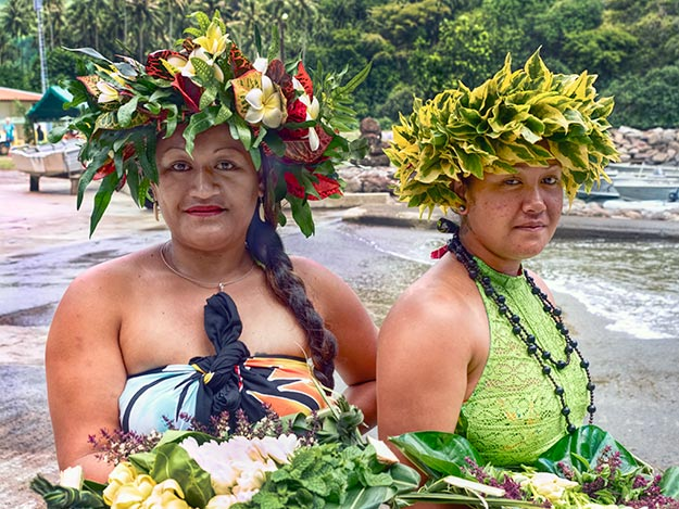 "Two beautiful Polynesian women at the dock on Fatu Hiva in the Marquesas Islands show off their handmade ""umu hei"" headdresses"