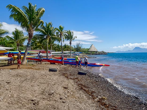 Racing teams haul their long, skinny outrigger canoes out of the water at Jardins de Paofai Park in Papeete