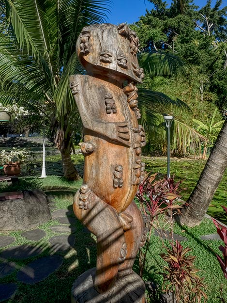 Giant carved Tiki, symbol of the spiritual life and power in Tahiti, stands at the edge of Queen's Pond in Papeete