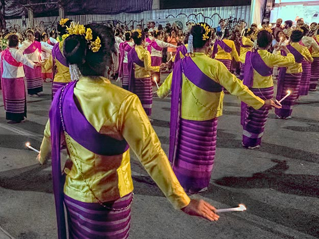 Holding lighted candles, Thai dancers perform the graceful candle dance at the opening ceremonies of Loy Krathong Festival