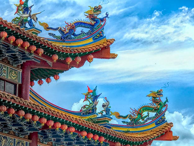 Brilliant ceramic dragons mounted on the up-swept roof beams of the pagodas at Thean Hou Temple