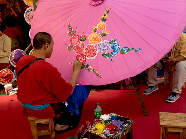 Artist paints a giant handmade paper umbrella at the Bo Sang Umbrella Festival
