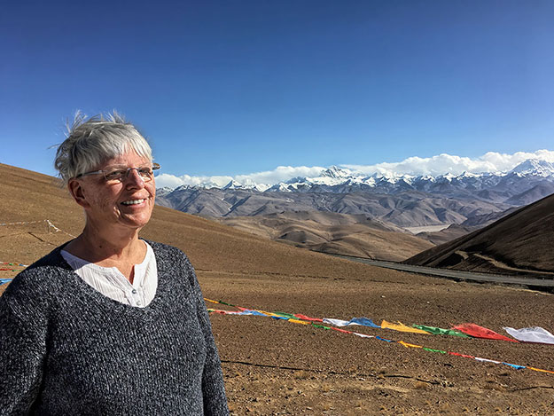 Barbara Weibel at Geu La Pass in Tibet with Mount Everest and the Himalayan Range in the background