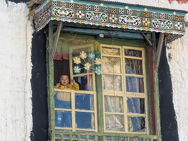 Toddler peers from the window of a traditional Tibetan home in the Old Town area of Gyantse, Tibet