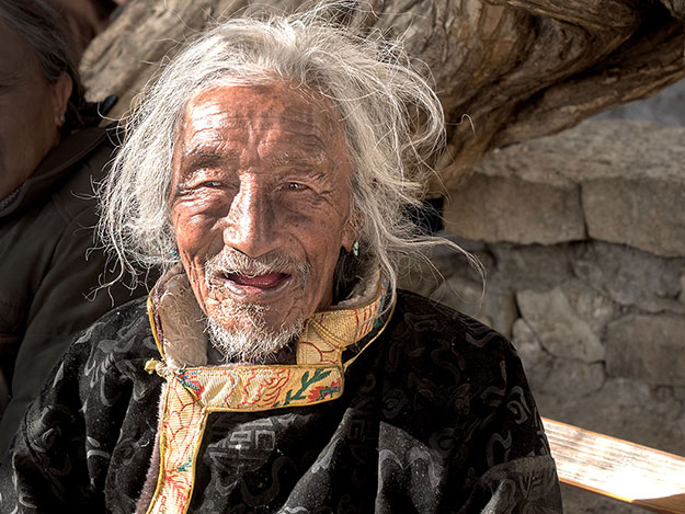 85 year-old man from the Shigatse region of Tibet visits Tashilhunpo Monastery to perform circumambulation of a revered stupa on the grounds