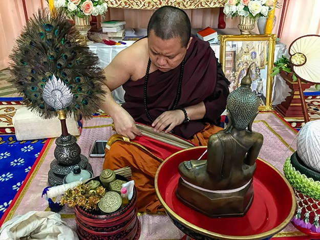 Phrapalad Thanwa Khayantam unwraps Buddhist scriptures to use in the Buddha statue consecration ceremony