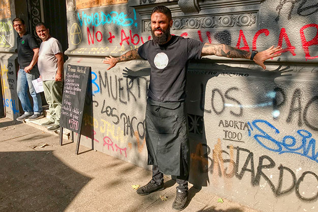 My server, Santiago, explains the meaning of many of the slogans painted on the walls of his restaurant in Santiago, Chile