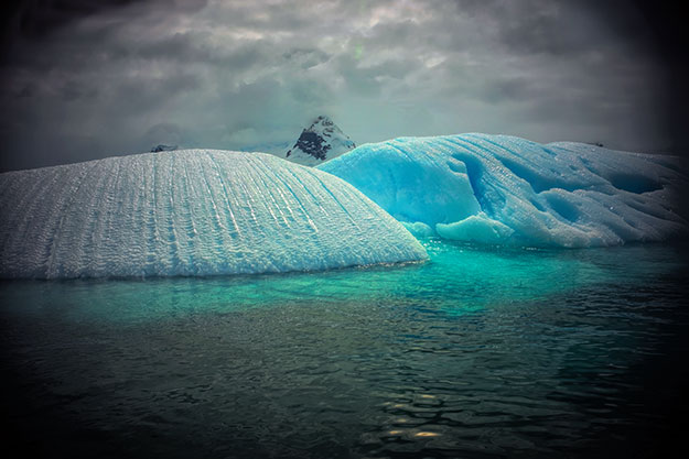 Overturned iceberg in Cierva Cove exposes the bottom, from where ancient air escapes as the ice melts