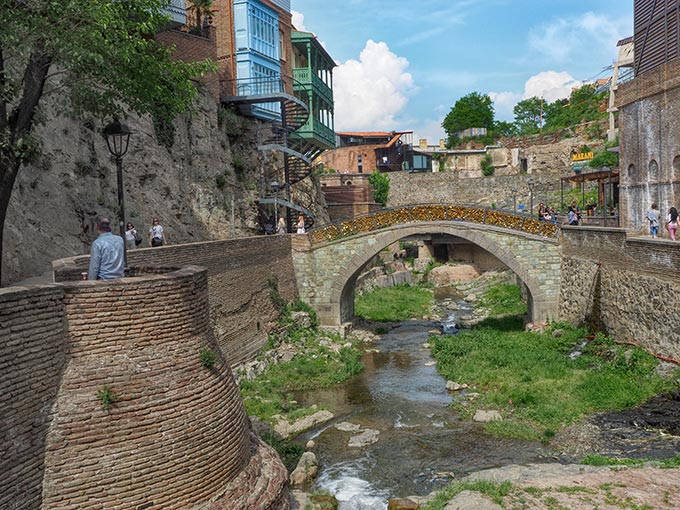 Love lock bridge along Samarkhakhevi Creek, with two of the few old wooden houses that still remain in Tbilisi
