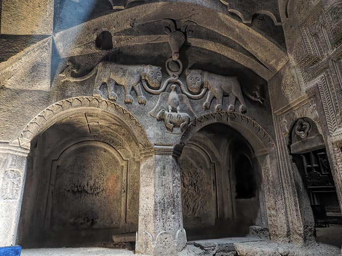 Visiting Armenia - Detailed images carved from solid stone inside Geghard Cave and Monastery in the Armenian countryside