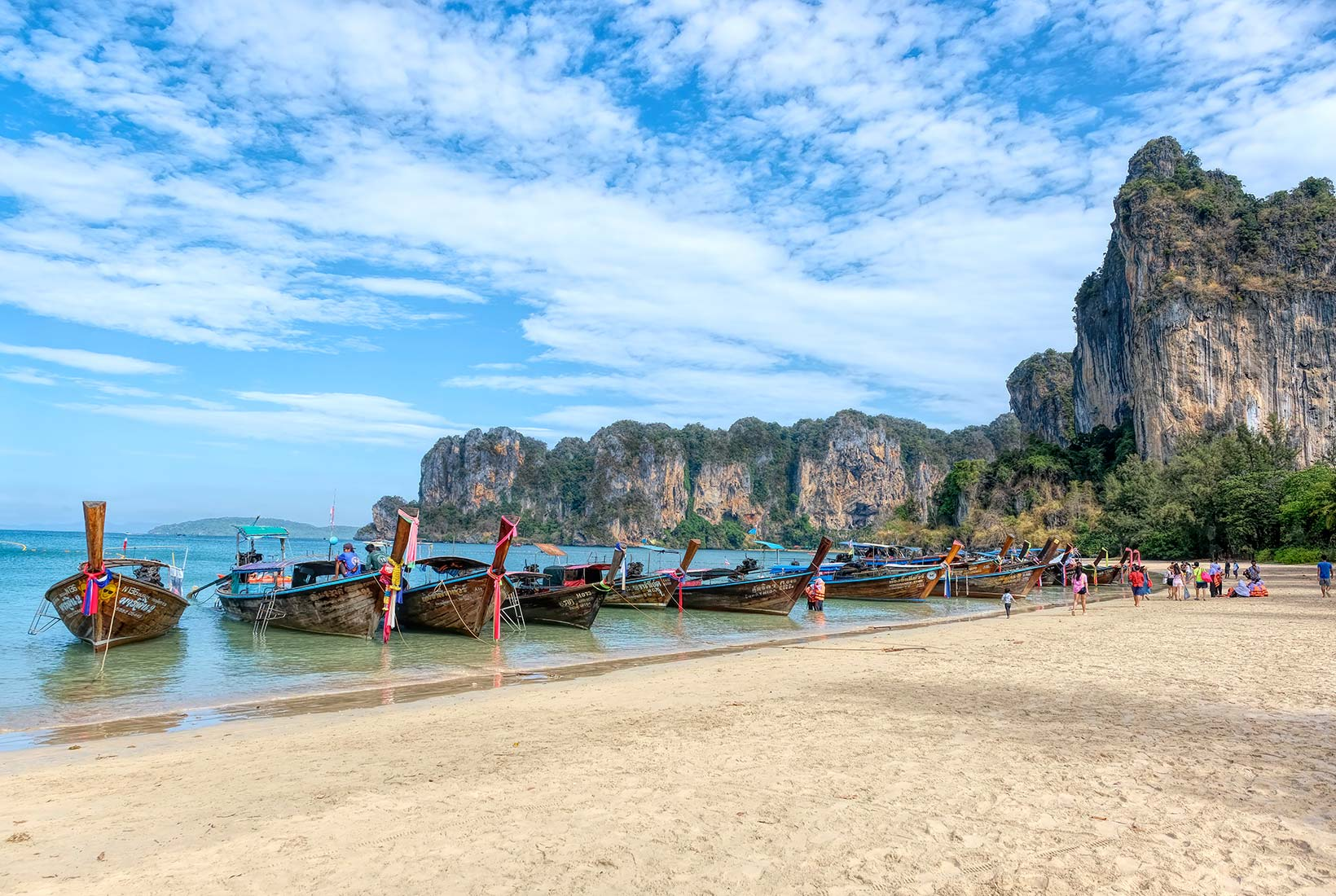 Longtail boats lined up, awaiting passengers on Railay Beach West